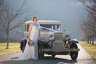 Beautiful bride with her vintage wedding car