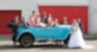 Bride, groom and bridal party with unique wedding car