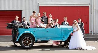 Bride, groom and bridal party with unique wedding car