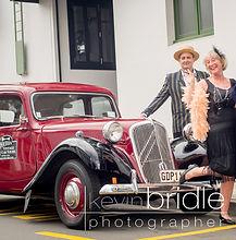 A couple Deco'ed up having photo shoot with Art Deco car