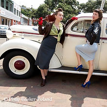 Models posing during a photoshoot with retro car