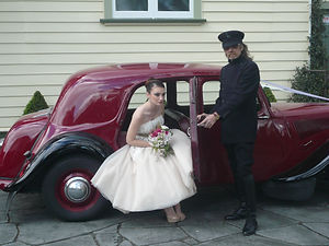 Vintage chauffeur helps bride out of Classic french wedding car