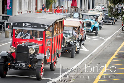Vintage bus on tour in Napier with a convoy of classic cars.