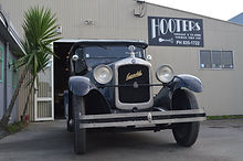 Old timer retro car outside Hooters Vintage car showroom in Napier