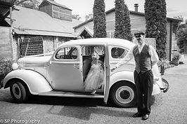 Young bridesmaid climbingout of classic wedding car