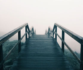 black and white image of wood stairs going down into dense fog