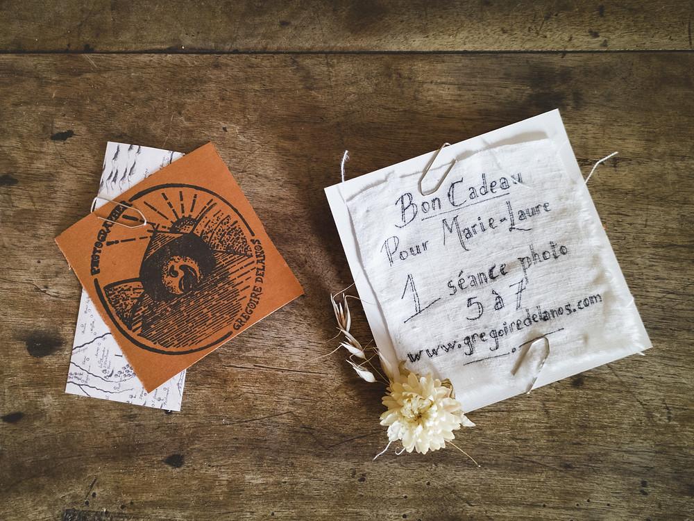bon cadeau fait main avec des matériaux recyclé : tissu, carton, tampon du logo réalisé par une artisan, illustrations de cartes anciennes, fleurs séchées.