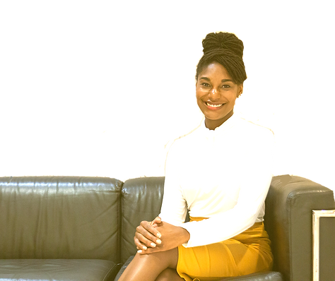 Picture shows an African-American( Tiffani Jackson) sitting on the right side of a swamp-green leather couch. The Tiffani's head is facing forward with her leg crossed over each other. Her hands rest on top of each other with white nail polish on her nails. She is wearing a mustard yellow tight-fitting skirt that comes up over her knee and a white blouse that is tucked in to the skirt. She is smiling with her teeth showing and has medium-thick curved eyebrows. Tiffani has her haired tied up in a large bun with her bang over her right eyebrow. The background is white.