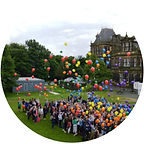 A crowd of people on a school field releasing balloons of many different colours.