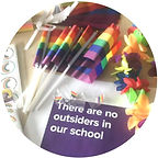 """Several rainbow flags with rainbow flag pins. Below is a message that reads """"There are no outsiders in our school""""."""
