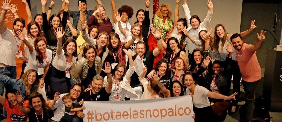 varias mulheres juntas comemorando com uma faixa bota elas no palco_edited.jpg