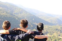 tres-meninos-abracados-olhando-para-o-horizonte-no-topo-da-montanda-do-voador.jpg