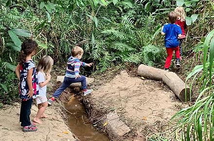 5-criancas-andando-na-floresta-e-pulando-uma-poca-dagua.jpg