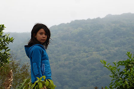 crianca-com-uma-blusa-azul-no-topo-da-montanha-olhando-para-a-foto.jpg