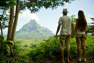Tahiti Trip Planner | GeoLuxe Travel | couple hiking in front of mountain
