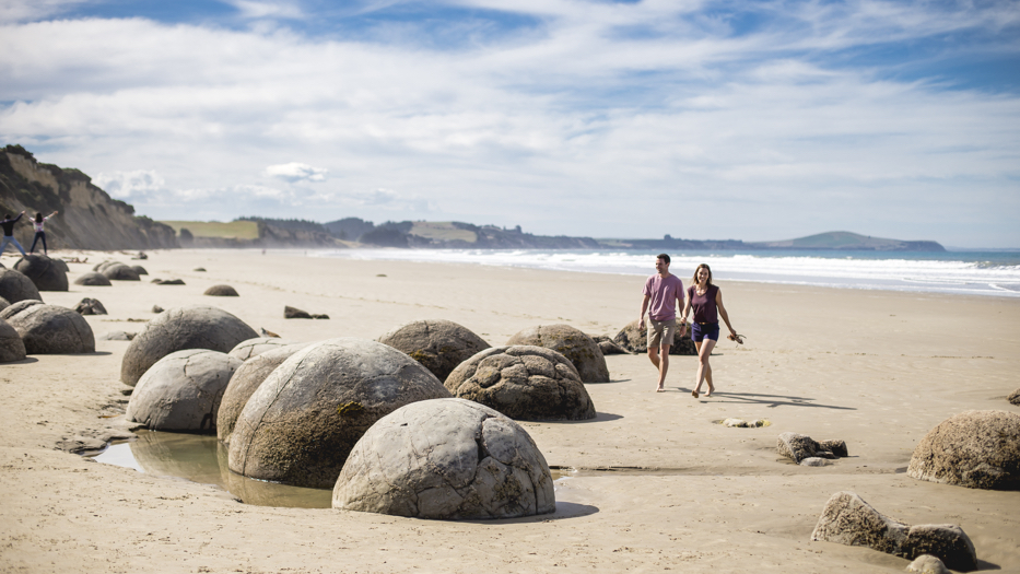 New Zealand Trip Planner | GeoLuxe | couple walking on rocky beach
