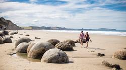 New Zealand Trip Planner   GeoLuxe   couple walking on rocky beach