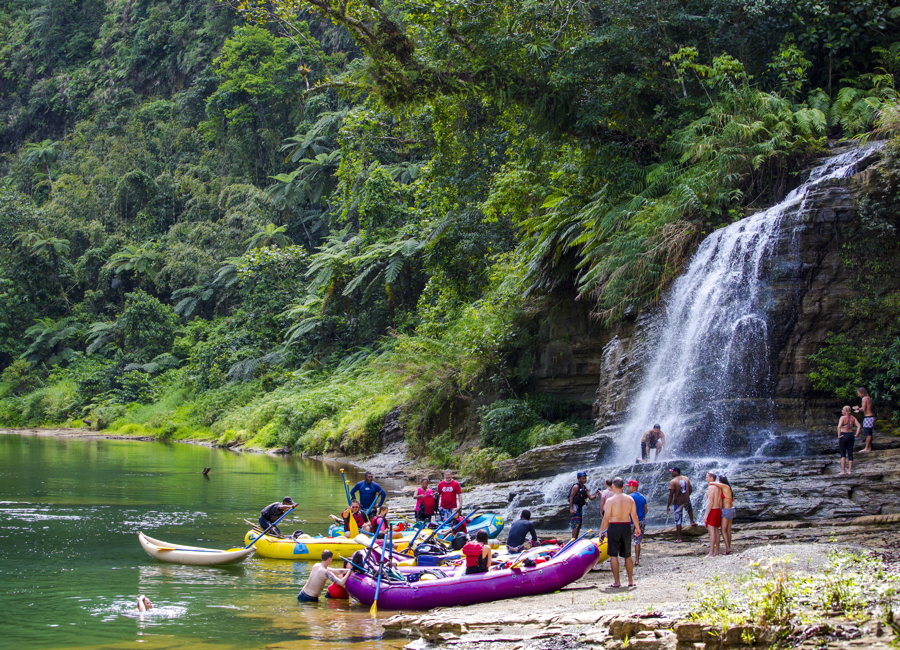 Fiji Trip Planner | GeoLuxe Travel | people in boats near a waterfall