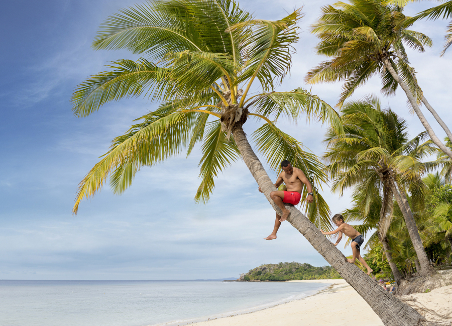 Fiji Trip Planner | GeoLuxe Travel | man on a palm tree