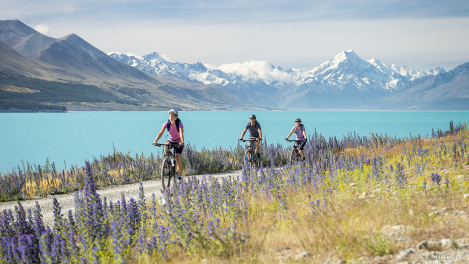 New Zealand Trip Planner | GeoLuxe | people biking in front of a lake and mountains