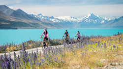 New Zealand Trip Planner   GeoLuxe   people biking in front of a lake and mountains