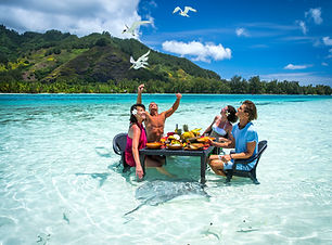 Tahiti Trip Planner | GeoLuxe Travel | people eating at table in the ocean