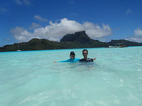 GeoLuxe Travel Testimonial | Couple swimming in the ocean | Luxury Travel Consultant