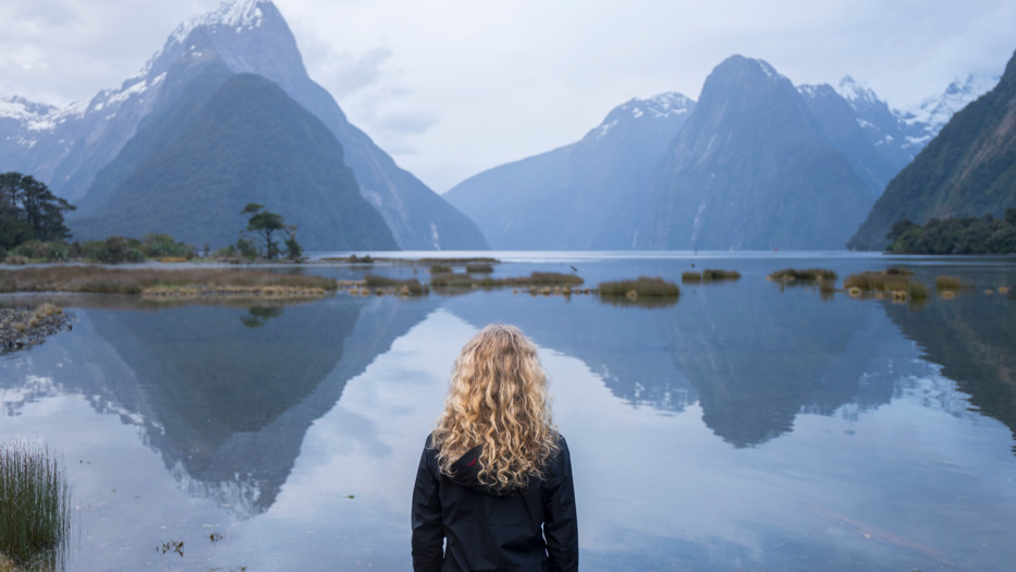 New Zealand Trip Planner | GeoLuxe | woman looking at lake and snowy mountains