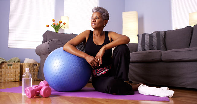 Senior Black woman sitting on floor with
