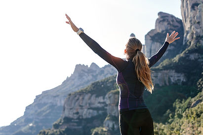 120983821-shot-of-trail-runner-with-open-arms-raised-while-enjoying-nature-on-mountain-pea
