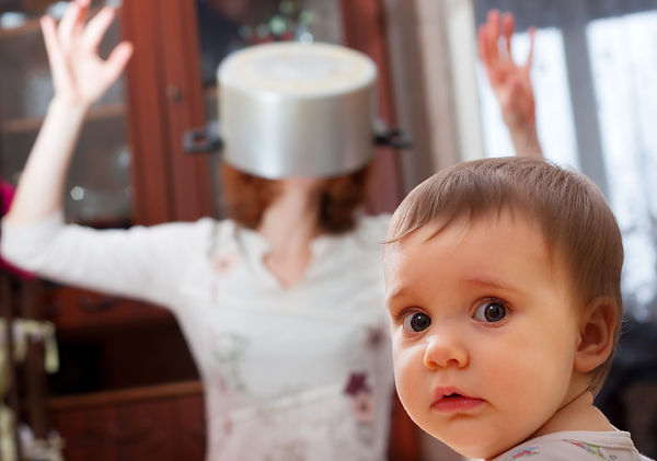 Portrait of scared baby against crazy mother with pan on head.jpg