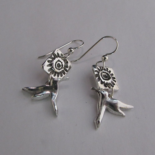 Handcrafted sterling silver flower and hummingbird earrings.