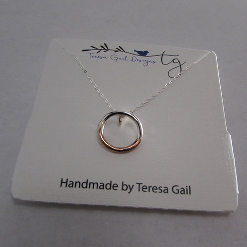Handcrafted sterling silver and copper circle necklace.
