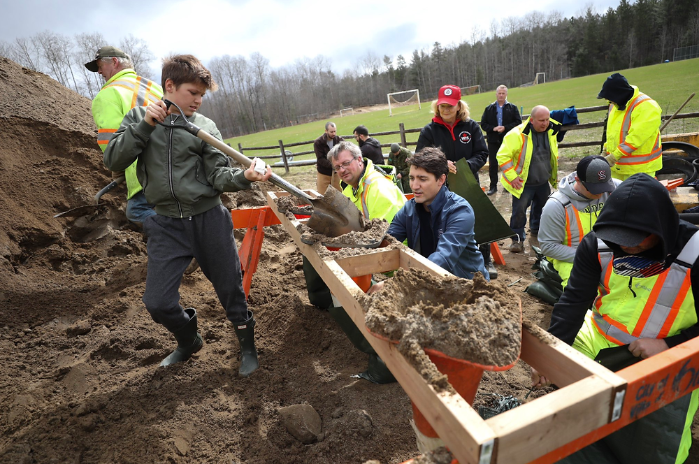 Trudeau, along with his sons Xavier and Hadrien fill sandbags.