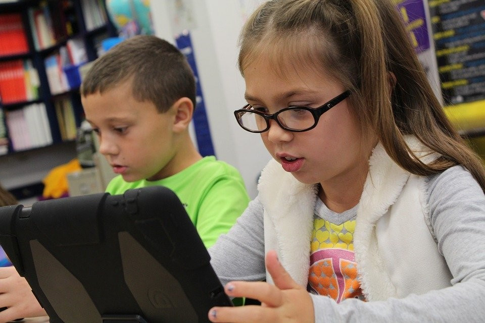 children using a tablet at home to access online learning tools provided through online tutoring