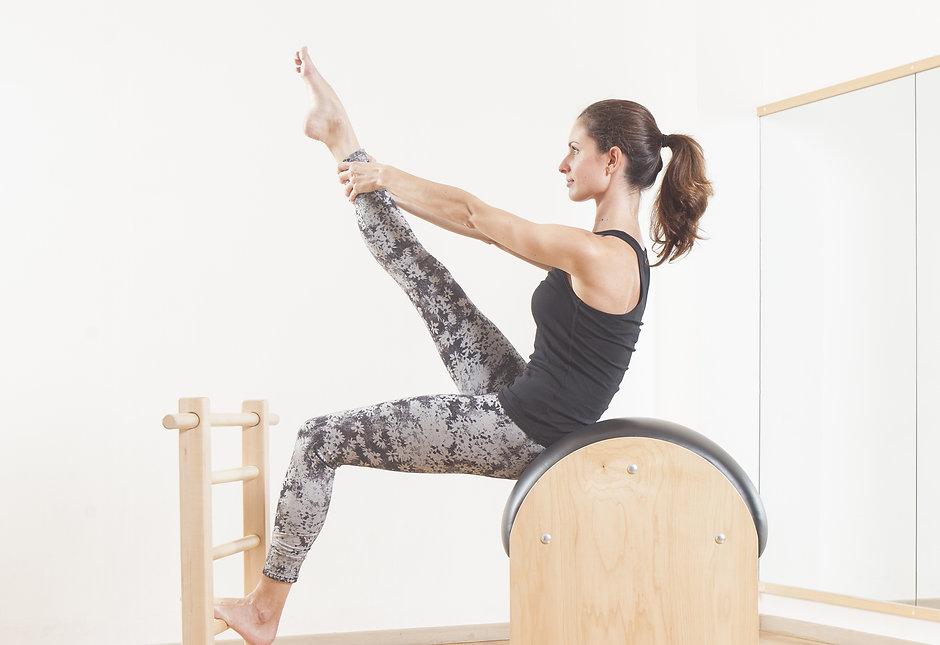 Beautiful woman performing pilates exerc
