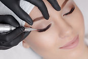 Cosmetologist making permanent makeup, c