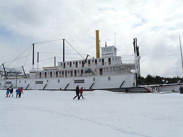 Lieu historique, le bateau S.S. Klondike à Whitehorse. Quelques personnes marchent sur la neige devant le bateau.