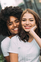 photo-of-two-women-smiling-wearing-white