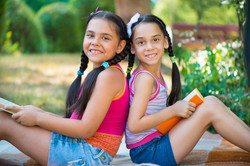 Hispanic sisters reading book in summer