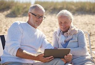happy senior couple with tablet closed title