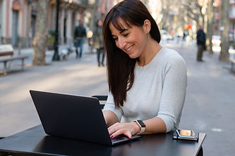Smiling woman using laptop at cafe terra