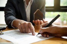 Real estate agent with house model hand putting signing contract,have a contract in place