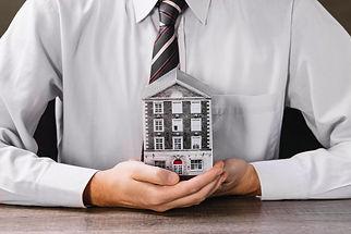 man-holding-miniature-house-hands.jpg