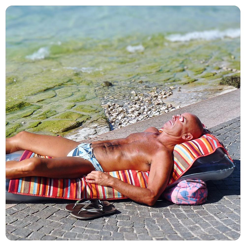 Bronzage intensif d'un touriste sur une plage italienne