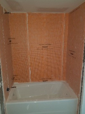 Tub scuffs and plaster drips from tile backboard work require scraping/cleaning