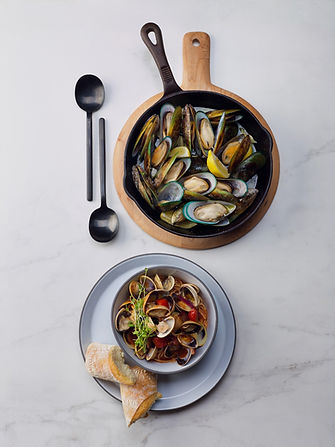 greenshell mussels in pan with serving spoons