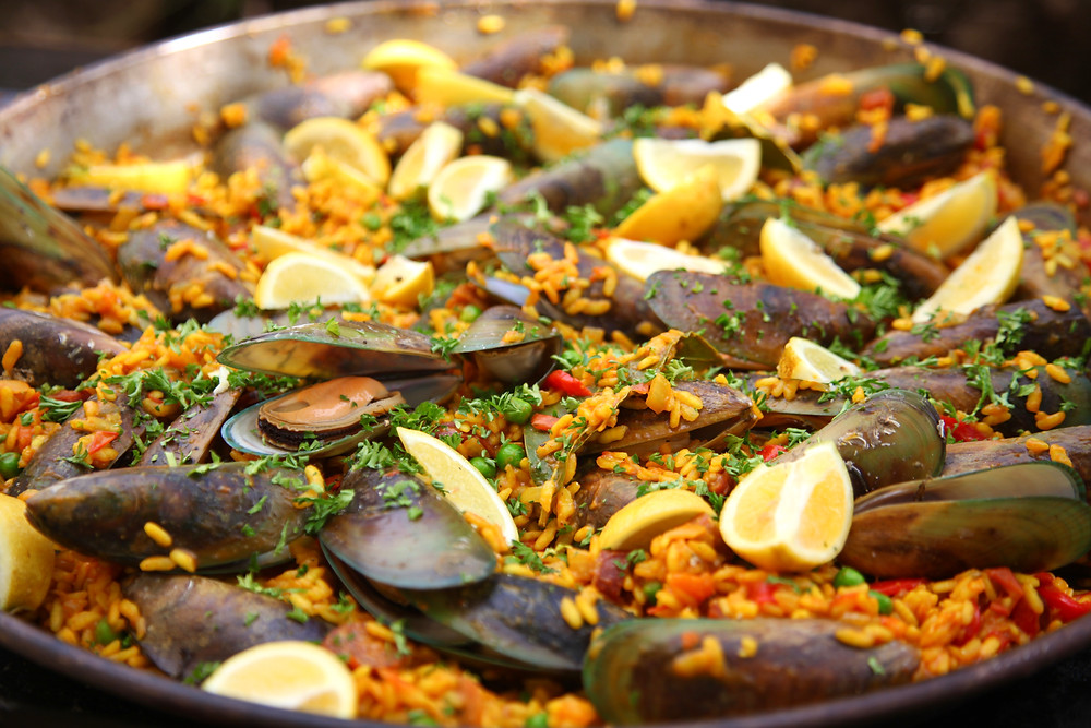 vibrant mussel BBQ paella in a paella pan with lemon