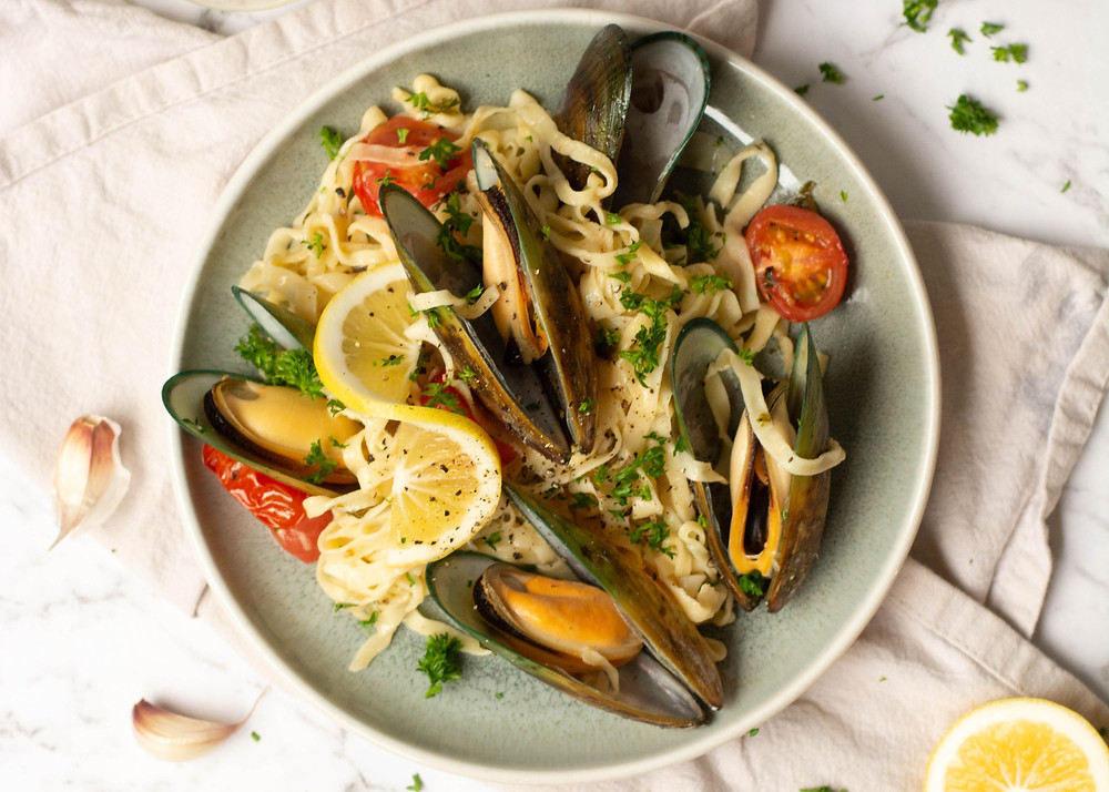 Mussels, pasta, tomatoes and lemon in a bowl on a table cloth
