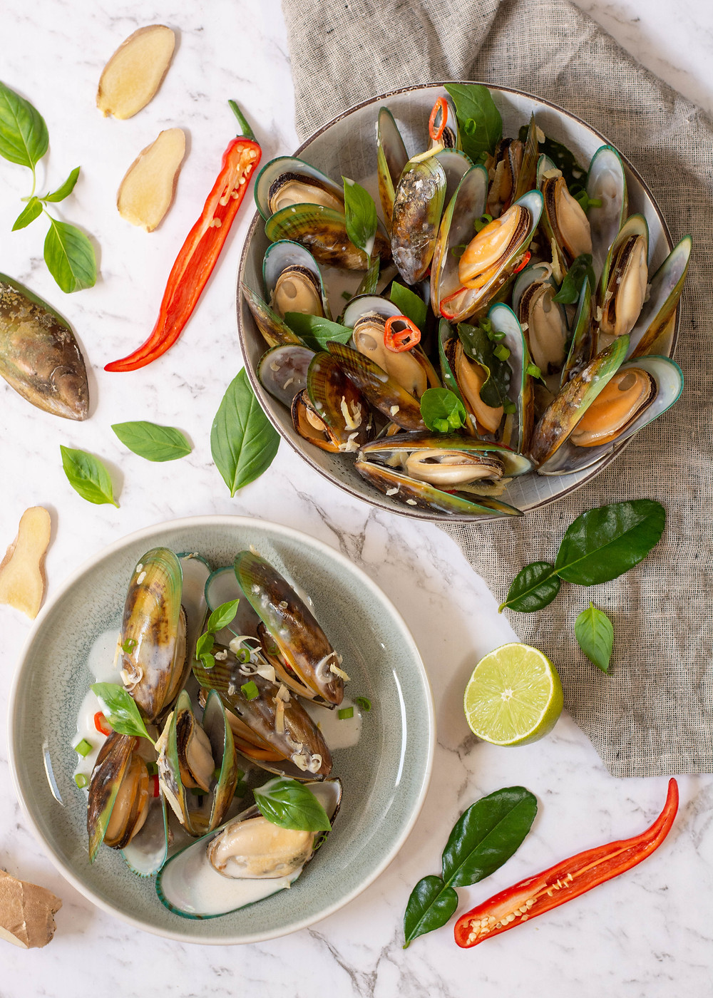 colourful lemongrass mussel broth in a bowl on a marble benchtop
